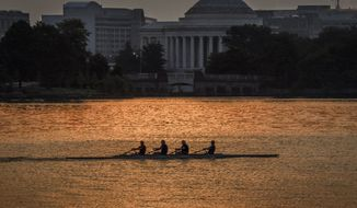 Rowers along the sun glistened Potomac River pass the Jefferson Memorial as another hot day dawns in Washington, Friday, July 14, 2017. (AP Photo/J. David Ake)