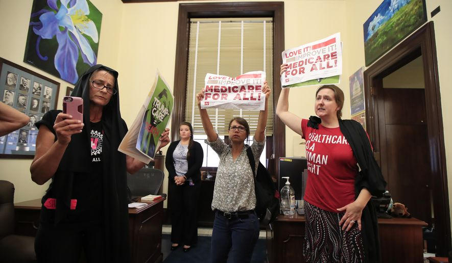 Protesters against the Republic health care proposals chant slogans and wave protest banners inside the office of Sen. Cory Gardner, R-Colo., at the Russell Senate Office building on Capitol Hill in Washington, Wednesday, July 19, 2017. (AP Photo/Manuel Balce Ceneta)
