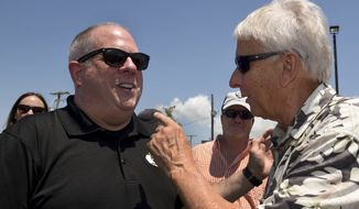 Gov. Larry Hogan is greeted by Jay Tawes, the grandson of Gov. J. Millard Tawes, at the 41st annual J. Millard Tawes Crab and Clam Bake in Crisfield, Md., Wednesday, July 19, 2017. (Amy Davis/The Baltimore Sun via AP)
