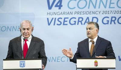 Israeli Prime Minister Benjamin Netanyahu, left, listens to Hungarian Prime Minister Viktor Orban during a press conference held after the talks of Netanyahu with heads of government of the Visegrad Group or V4 countries in the Pesti Vigado building in Budapest, Hungary, Wednesday, July 19, 2017. Netanyahu is staying on a four-day official visit in Hungary. (Balazs Mohai/MTI via AP)