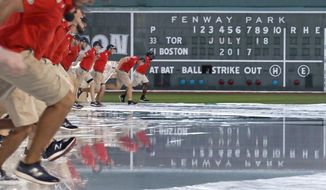 The grounds crew removes the tarp, completely filled with rain water, after a heavy storm passed over prior to a baseball game between the Boston Red Sox and Toronto Blue Jays at Fenway Park in Boston, Tuesday, July 18, 2017. The start of the game was delayed for about an hour. (AP Photo/Charles Krupa)