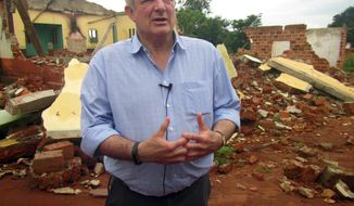 In this photo taken on Tuesday July 18, 2017, U.N. humanitarian chief Stephen O'Brien answers reporters' questions during an organized trip to Bangassou, Central African Republic. O'Brien insisted that the U.N. is there to help, and he warned of the growing violence. More than 300 people have been killed and 150,000 displaced since mid-May as violence that began in 2013 moves into the impoverished country's central and southeastern regions. (AP Photo/Hyppolite Marboua)