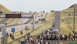 A highway sign warns drivers along Interstate 25 not to stop during a cattle drive on Hynds Boulevard during the annual 121st Cheyenne Frontier Days cattle drive on Sunday morning, July 16, 2017 in Cheyenne, Wyo. More than 500 head of cattle were driven from Horse Creek Road down to Frontier Park, with hundreds of spectators lining the roads. (Jacob Byk/Wyoming Tribune Eagle via AP)