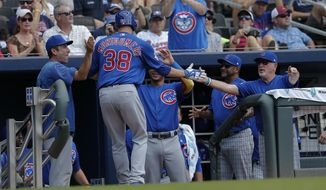 Chicago Cubs pitcher Mike Montgomery (38) is greeted at the dugout by teammates including manager Joe Maddon, right, after hitting a home run in the fifth inning of a baseball game against the Atlanta Braves, Wednesday, July 19, 2017, in Atlanta. (AP Photo/John Bazemore)
