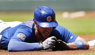 Chicago Cubs third baseman Kris Bryant (17) holds his finger after being injured diving into third base in the first inning of a baseball game against the Atlanta Braves Wednesday, July 19, 2017, in Atlanta. (AP Photo/John Bazemore)