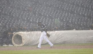Chicago White Sox's Alen Hanson makes his way past the grounds crew as a heavy storm causes a rain delay during the eighth inning of a baseball game between the White Sox and the Los Angeles Dodgers on Wednesday, July 19, 2017, in Chicago. (AP Photo/Charles Rex Arbogast)