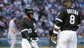 Chicago White Sox's Yoan Moncada (10) smiles at first base coach Daryl Boston after drawing a walk from Los Angeles Dodgers starting pitcher Kenta Maeda, lef rear, during the second inning of a baseball game Wednesday, July 19, 2017, in Chicago. (AP Photo/Charles Rex Arbogast)