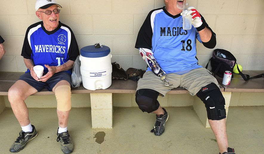In a Monday, July 10, 2017 photo, Angelo Malizial, left, and friend John Lancaster joke around between innings before a game at School Road Park in Hatfield, Pa. On Tuesday, Malizial turned 90-years-old. He's the oldest member on his league. (Rick Kintzel/The Intelligencer via AP)