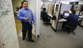 In this June 30, 2017 photo, Al Rodriguez walks to his desk in the call center at Bold Sale Solutions, a subsidiary of Dallas Lighthouse of the Blind in Dallas. (Nathan Hunsinger/The Dallas Morning News via AP)