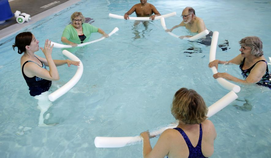 ADVANCE FOR SATURDAY JULY 22 AND THEREAFTER - In a Friday, July 7, 2017 photo, Amy Free, left, uses American Sign Language as she teaches a water exercise class for deaf people at UW Health at the American Center in Madison, Wis. (Amber Arnold/Wisconsin State Journal via AP)