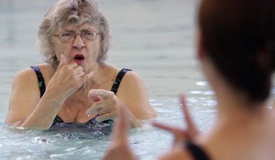 ADVANCE FOR SATURDAY JULY 22 AND THEREAFTER - In a Friday, July 7, 2017 photo, Ann Marie Hathway, 83, of Madison, who is deaf, signs to swim instructor Amy Free during a water exercise class that is taught in American Sign Language at UW Health at the American Center in Madison, Wis. (Amber Arnold/Wisconsin State Journal via AP)