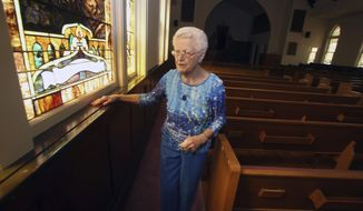 ADVANCE FOR WEEKEND EDITIONS, JULY 22-23 - In this July 6, 2017, photo, long-time church member Joyce Heckman, 94, walks through the 133-year-old First Lutheran Church, in Waco, Texas. The once-vibrant church family boasted 450 members, requiring an extensive expansion project that more than doubled the size of the building in 1958. Now with only 40 worshipers on Sunday morning, the church will be sold to an up-and-coming Anglican congregation. (Jerry Larson/Waco Tribune-Herald via AP)