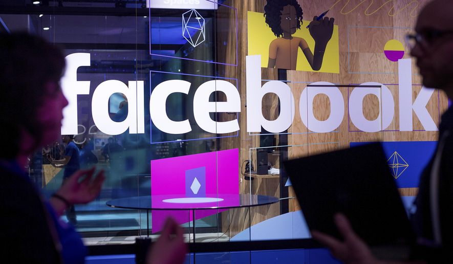 In this April 18, 2017, file photo, conference workers speak in front of a demo booth at Facebook's annual F8 developer conference in San Jose, Calif. (AP Photo/Noah Berger, File)