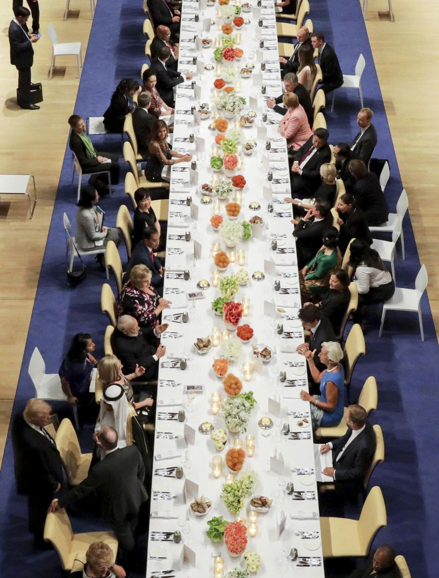 FILE - In this July 7, 2017 photo U.S. President Donald Trump, bottom left, talks to delegates from Saudi Arabia as his wife Melania talks to Russian Prseident Vladimir Putin with the help of a Russian translator, top right, as the heads of government of the G-20 states and their partners have dinner after a concert in the Elbphilharmonie concert hall in Hamburg, Germany (Kay Nietfeld/Pool Photo via AP)