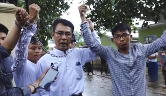 In this image made from video released by the Democratic Voice of Burma, left to right, Burmese journalists La Wei, from the Irrawaddy, Aye Nai, from the Democratic Voice of Burma, and Pyi Phone Aung, from the Democratic Voice of Burma raise their chained wrists decrying the lack of freedom and democracy as they leave the court after facing charges of unlawful association, Tuesday, July 18, 2017, in Hsipaw, Shan state, Myanmar. The video was recorded Tuesday, and it underscores just how little has changed in this Southeast Asian country since former Nobel Laureate and longtime opposition leader Aung San Suu Kyi won elections last year. (Democratic Voice of Burma via AP)