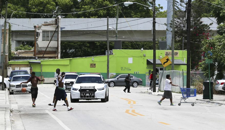 Police patrol a side street next to an apartment building where a 10-year-old boy that died of a fentanyl overdose last month lived, in Miami, Fla. (AP Photo/Mario Houben)