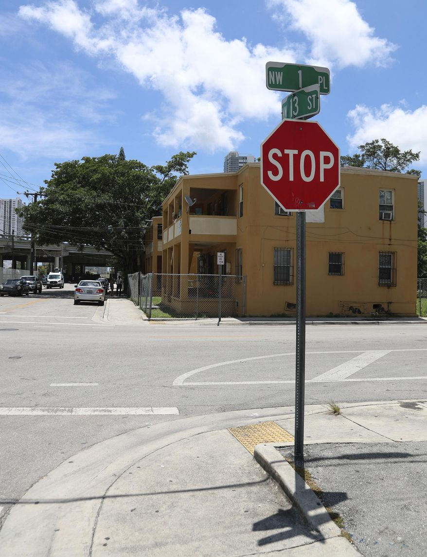 Cars sit parked in front of an apartment building where a 10-year-old boy, that died of a fentanyl overdose last month, lived in Miami, Fla. (AP Photo/Mario Houben)