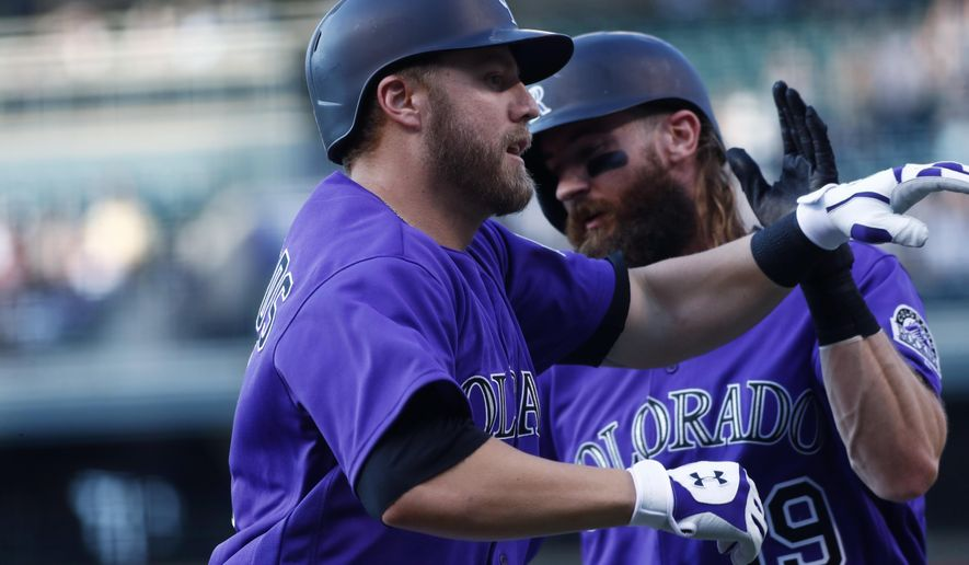Colorado Rockies' Mark Reynolds, front, is congratulated by Charlie Blackmon as Reynolds crosses home plate after hitting a three-run home run off San Diego Padres starting pitcher Dinelson Lamet in the first inning of a baseball game Tuesday, July 18, 2017, in Denver. (AP Photo/David Zalubowski)