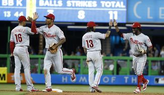 Philadelphia Phillies' Cesar Hernandez (16) Nick Williams, second from left, Freddy Galvis (13) and Odubel Herrera, right, celebrate after the Phillies defeated the Miami Marlins 5-2 during a baseball game, Tuesday, July 18, 2017, in Miami. (AP Photo/Wilfredo Lee)