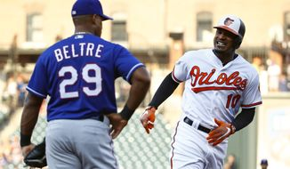 Baltimore Orioles' Adam Jones, right, smiles at Texas Rangers third baseman Adrian Beltre as he rounds third base after hitting a solo home run in the first inning of a baseball game in Baltimore, Wednesday, July 19, 2017. (AP Photo/Patrick Semansky)