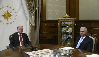 Turkey's President Recep Tayyip Erdogan, left, meets with Turkey's Prime Minister Bibali Yildirim, right, in Ankara, Turkey, Wednesday, July 19, 2017. (Presidency Press Service via AP, Pool)