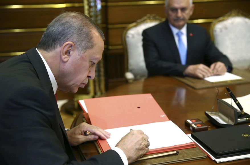 "Turkey's President Recep Tayyip Erdogan, left, signs the new cabinet document, as Turkey's Prime Minister Bibali Yildirim, right, looks on, following their surprise meeting in Ankara, Turkey, Wednesday, July 19, 2017. Yildirim announced a cabinet reshuffle, replacing or swapping 11 ministers in the 26-member council of ministers. Erdogan has complained of a ""fatigue"" within the ruling party, speaking of a need for rejuvenation. (Presidency Press Service/Pool Photo via AP)"