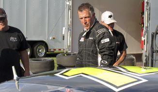 In this July 6, 2017, photo, Vermont Gov. Phil Scott walks beside his stock car at the Thunder Road race track in Barre, Vt., where he won the evening's 50-lap feature race, his 30th lifetime win. Scott spends most of his time working as governor, but he still tries to race whenever he can. (AP Photo/Wilson Ring) ** FILE **