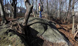 In this Jan. 11, 2016 file photo, Salem State University history professor Emerson Baker walks through an area known as Proctor's Ledge that he and a team of researchers said is the exact site where innocent people were hanged during the 1692 witch trials in Salem, Mass. Salem and Danvers are holding separate ceremonies Wednesday, July 19, 2017, to mark the 325th anniversary of the hangings of five women convicted of being witches. Twenty people in all were killed. (Ken Yuszkus/The Salem News via AP, File)