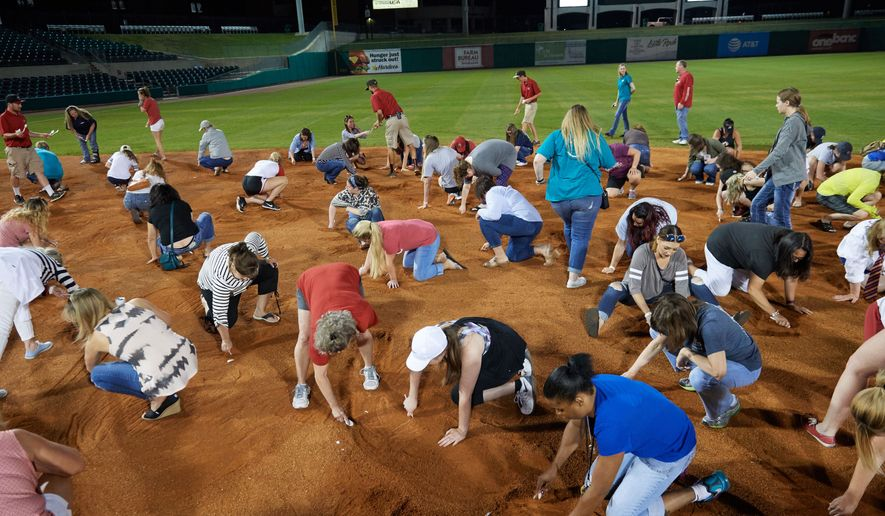 """Arkansas Travelers female fans search the infield for a buried diamond ring during the teams annual """"Diamond Dig"""", presented by Lee Ann's Fine Jewelry, after a game against the Midland RockHounds on May 25, 2017 at Dickey-Stephens Park in Little Rock, Arkansas.  Midland defeated Arkansas 8-1.  (Mike Janes/Four Seam Images via AP)"""