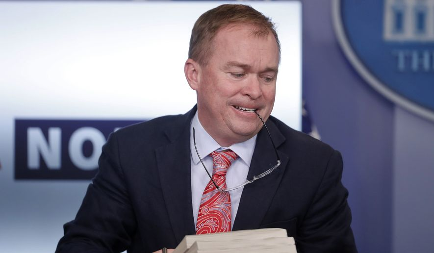 White House Budget Director Mick Mulvaney showed a pile of Federal Registers from the time of the Obama administration on Thursday. (Associated Press)