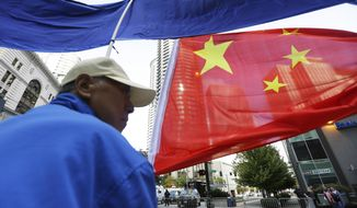 A demonstrator with the Falun Gong protest group stands near the hotel where Chinese President Xi Jinping is staying Tuesday, Sept. 22, 2015, in downtown Seattle. Xi is stopping in Seattle on his way to Washington, D.C., for a White House state dinner on Friday. (AP Photo/Ted S. Warren)