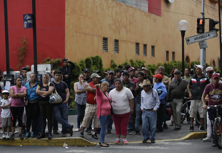 ADDS LOCATION - People watch security forces gather around the Nopalera metro station in the area where a suspected drug gang leader and seven others were killed earlier in the day, according to the Navy, in the Tlahuac neighborhood of Mexico City, Thursday, July 20, 2017. In a statement Thursday, the Navy said a gang of street-level drug dealers operated in the Tlahuac and Iztapalapa districts on the city's south and east sides, where it dealt drugs, as well as carried out kidnappings, extortion and murder. (AP Photo/Rebecca Blackwell)