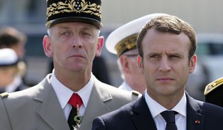 French President Emmanuel Macron, right, and new French armed forces chief of staff Francois Lecointre review an honor guard at the air force base in Istres, southern France, Thursday, July 20, 2017. Macron's visit to the Istres air base Thursday comes the day after the head of the French military quit in a dispute with Macron over budget cuts. (Arnold Jerocki, Pool via AP)