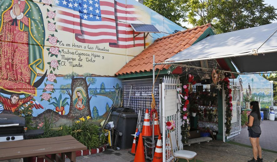 In this Tuesday, July 18, 2017 photo, Jennifer Moreno offers prayers at a shrine to the Virgen of Guadalupe in Passaic, N.J. Passaic, a city 12 miles from Manhattan, has become a second Puebla for many Mexicans who moved here from the state of Puebla in search of a better life. (AP Photo/Seth Wenig)