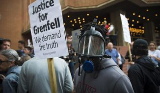 People protest ahead of a meeting of Kensington and Chelsea Council at Kensington Town Hall in west London, Wednesday July 19, 2017, the local authority in control of response to the recent Grenfell Tower fire.   The fire at the Grenfell Tower residential bloc left dozens dead (Ben Stevens/PA via AP)