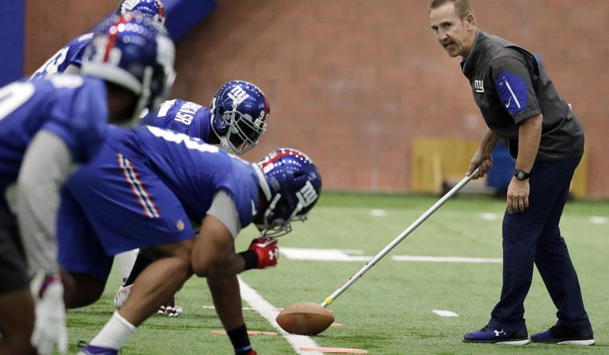 In this May 25, 2017, file photo, New York Giants defensive coordinator Steve Spagnuolo, right, runs a drill with his players during the team's organized team activities at its NFL football training facility in East Rutherford, N.J. When 10 years' worth of labor peace came to the NFL in 2011, so did a massive change in the rules governing practice, during the season, the offseason and, most especially, in training camps. (AP Photo/Julio Cortez, File)