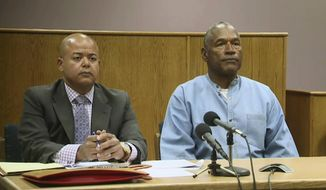 Former NFL football star O.J. Simpson appears with his attorney, Malcolm LaVergne, left, via video for his parole hearing at the Lovelock Correctional Center in Lovelock, Nev., on Thursday, July 20, 2017.  Simpson was convicted in 2008 of enlisting some men he barely knew, including two who had guns, to retrieve from two sports collectibles sellers some items that Simpson said were stolen from him a decade earlier. (KOLO-TV via AP, Pool)