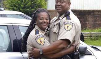"In this Tuesday, July 18, 2017 photo, Lt. Benedict ""Bena"" Williams, left, and her fiance Jerry Jones Jr., both deputies with the Pike County Sheriff's Department, pose for a photo at their house in the county. The Enterprise-Journal reports that Williams and Jones are marrying Saturday in McComb, Miss. (LaKeadra Coffey/The Enterprise-Journal via AP)"