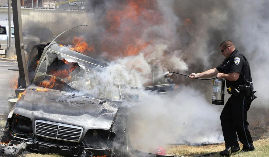 Alton police officer Ryan Parker uses a fire extinguisher to try to slow the flames engulfing a car that crashed Thursday July 20, 2017, in Alton, Ill., as two people are inside. Firefighters were able to pull the driver free, but both occupants were flown to a St. Louis hospital. (John Badman/The Telegraph via AP)