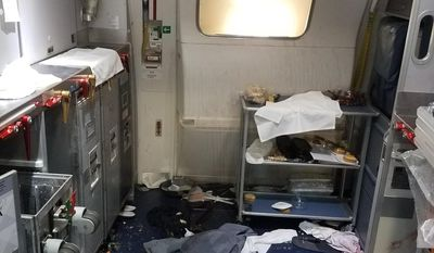 FILE - This Friday, July 7, 2017 file photo taken by the FBI and released via the U.S. Attorney's Office in Seattle shows the aftermath of a cabin on Delta Flight 129 from Seattle to Beijing, after authorities say flight attendants struggled with Joseph Daniel Hudek IV, a passenger who lunged for an exit door. The photo was included in a criminal complaint filed July 7.  Prosecutors disclosed Thursday, July 20, that Hudek was indicted on five federal charges; one count of interfering with the flight crew and four counts of assault on an aircraft. (FBI via U.S. Attorney's Office in Seattle via AP, File)