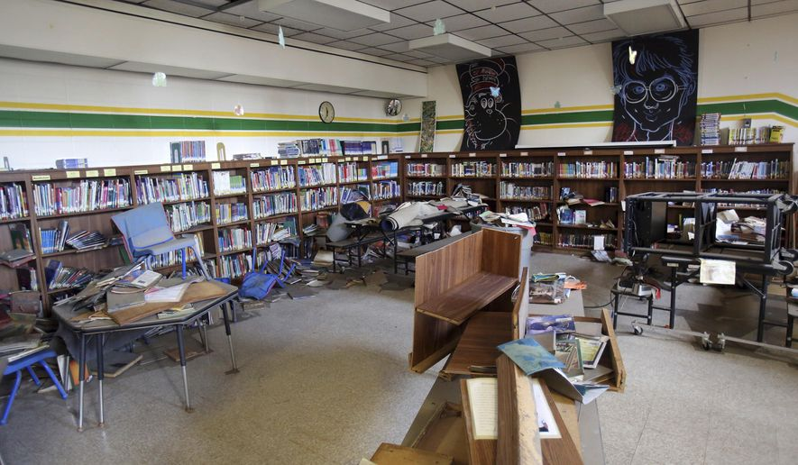 Flooding from heavy rains damaged the library at W.J. Murphy Elementary School in Round Lake, Ill. Illinois Gov. Bruce Rauner toured the flood damaged school on Wednesday. (Steve Lundy/Daily Herald via AP)