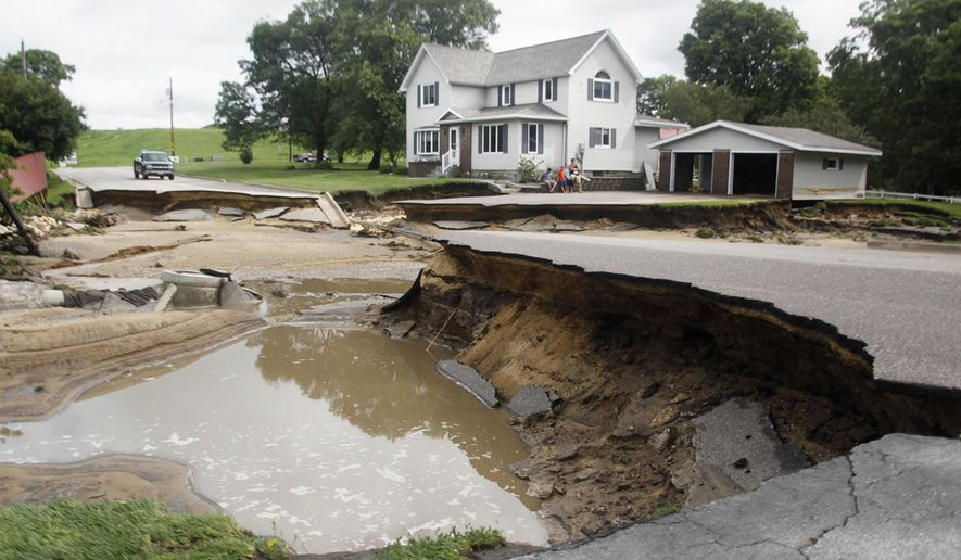 A section of North Oak Street is caved in and impassable Thursday, July 20, 2017, in Arcadia, Wis., following thunderstorms the night before that caused nearby Turton Creek to overflow its banks. Several hundred people evacuated their homes early Thursday in the small western Wisconsin community. (Chuck Miller/The Daily news via AP)