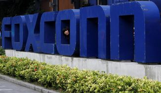 FILE - In this Thursday, May 27, 2010, file photo, a worker looks out through the logo at the entrance of the Foxconn complex in the southern Chinese city of Shenzhen. Two Republican state lawmakers said Thursday, July 20, 2017, that Wisconsin could announce it has landed a deal for Taiwanese iPhone manufacturer Foxconn to locate in the state as soon as the end of the month. (AP Photo/Kin Cheung, File)
