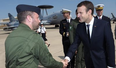 French President Emmanuel Macron, right, meets French troops at the air force base of Istres, southern France, Thursday, July 20, 2017. Macron's visit to the Istres air base Thursday comes the day after the head of the French military quit in a dispute with Macron over budget cuts. (Arnold Jerocki, Pool via AP)