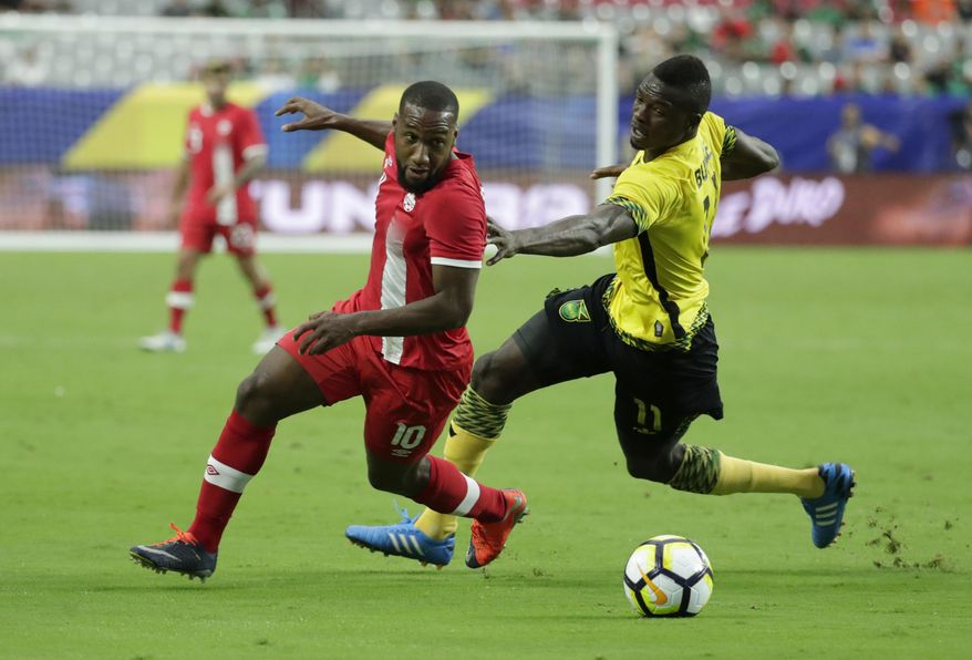 Canada's David Junior Hoilett, left, is chased by Jamaica's Cory Burke during a CONCACAF Gold Cup quarterfinal soccer match, Thursday, July 20, 2017, in Glendale, Ariz. (AP Photo/Matt York)