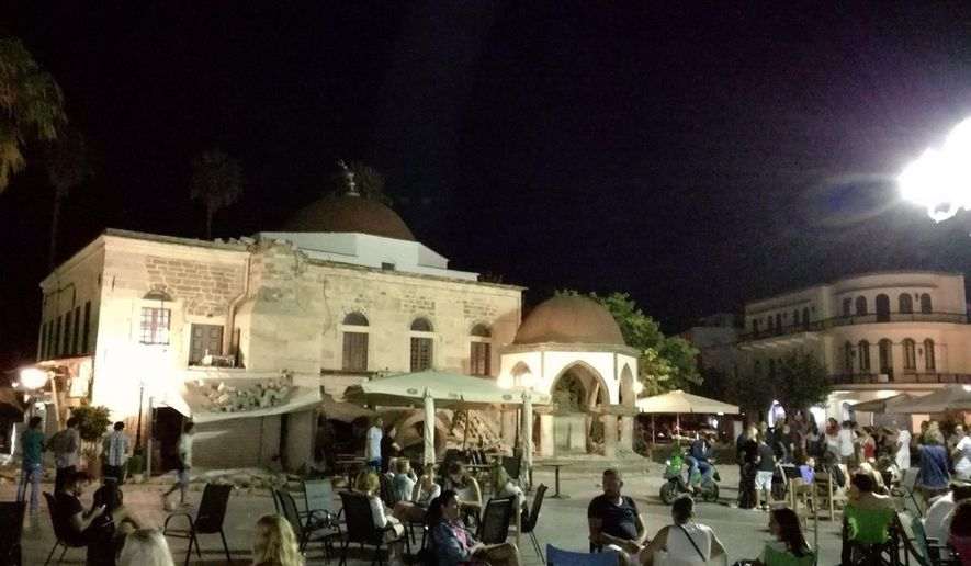 People sit at a square after an earthquake on the Greek island of Kos early Friday, July 21, 2017. A powerful earthquake struck Greek islands and Turkey's Aegean coast early Friday morning, damaging buildings and a port and killing at least two people, authorities said. (Kostoday.gr via AP)