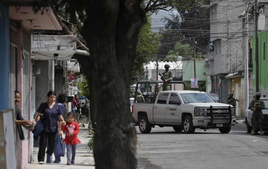 Marines block a street where the suspected leader of a drug gang and seven others were killed, according to the Navy, in southern Mexico City, Thursday, July 20, 2017. In a statement Thursday, the Navy said a gang of street-level drug dealers operated in the Tlahuac and Iztapalapa districts on the city's south and east sides, where it dealt drugs, as well as carried out kidnappings, extortion and murder. (AP Photo/Rebecca Blackwell)