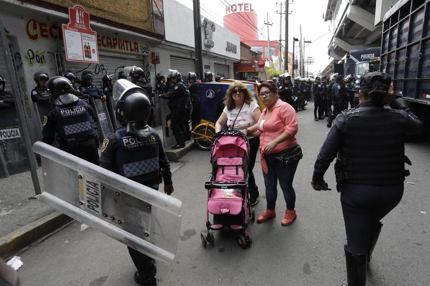 Women make their way past police surrounding the Noplera metro after the suspected leader of a drug gang and seven others were killed, according to the Navy, in the Tlahuac neighborhood of Mexico City, Thursday, July 20, 2017. In a statement Thursday, the Navy said a gang of street-level drug dealers operated in the Tlahuac and Iztapalapa districts on the city's south and east sides, where it dealt drugs, as well as carried out kidnappings, extortion and murder. (AP Photo/Rebecca Blackwell)
