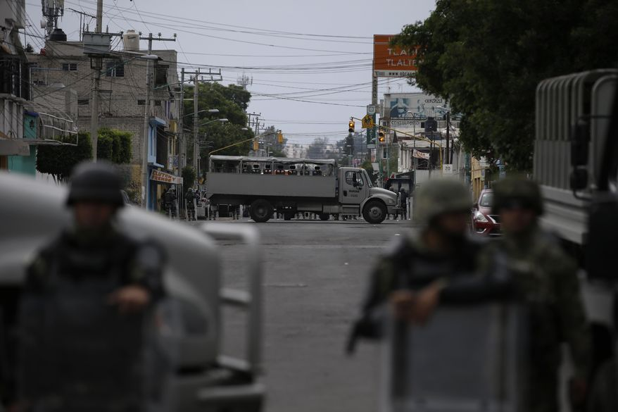 Marines block the area where a suspected drug gang leader and seven others were killed, according to the Navy, in the Tlahuac neighborhood of Mexico City, Thursday, July 20, 2017. In a statement Thursday, the Navy said a gang of street-level drug dealers operated in the Tlahuac and Iztapalapa districts on the city's south and east sides, where it dealt drugs, as well as carried out kidnappings, extortion and murder. (AP Photo/Rebecca Blackwell)