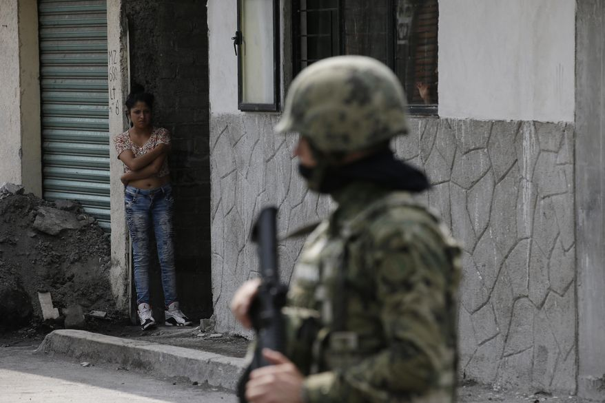 A woman peers out from a home as Marines block off the area where the suspected leader of a drug gang and seven others were killed, according to the Navy, in southern Mexico City, Thursday, July 20, 2017. In a statement Thursday, the Navy said a gang of street-level drug dealers operated in the Tlahuac and Iztapalapa districts on the city's south and east sides, where it dealt drugs, as well as carried out kidnappings, extortion and murder. (AP Photo/Rebecca Blackwell)